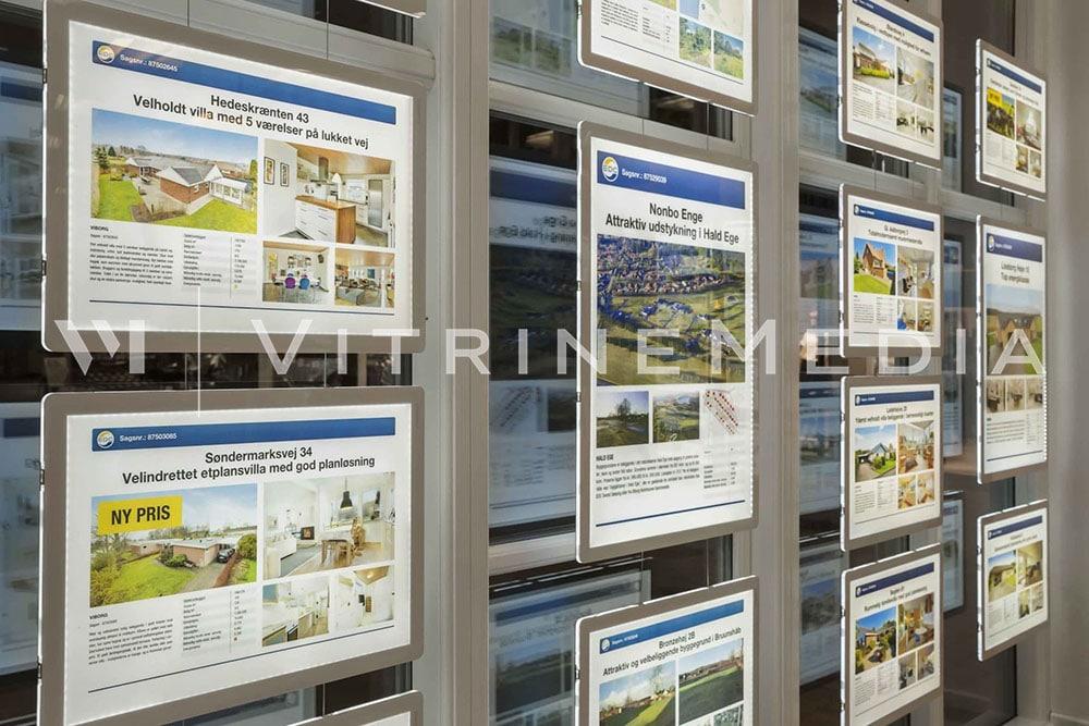Display LED suspenso iluminado instalado em vitrine da imobiliária EDC